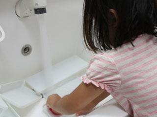 洗面所の掃除をする子供