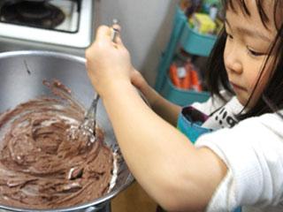 泡だて器でチョコを混ぜる女の子