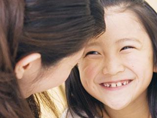 笑顔の子供と話しかける母親