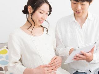 妊婦の妻にタブレットを見せる夫