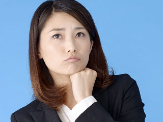 顎にこぶしを当てて眉間に皺をよせる女性