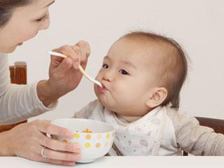 赤ちゃんにスプーンで食べさせる母親