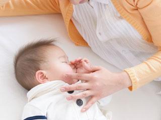 眠る赤ちゃんの傍で見守る母親