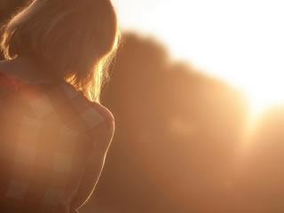 離婚後の寂しさに夕日を眺める孤独な女性