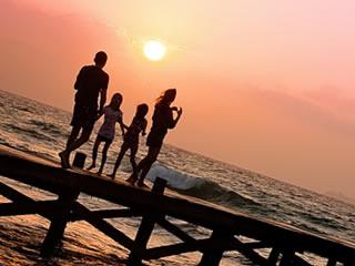 夕暮れに家族で桟橋を渡る仲良し親子