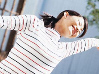 朝、手を広げて背伸びする女性