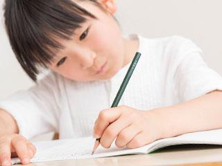 鉛筆でノートに字を書く児童