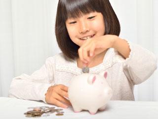 硬貨を貯金する子供
