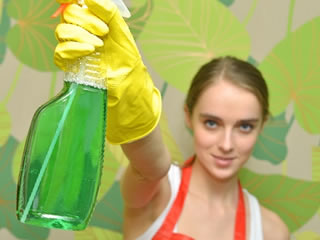 セスキ炭酸ソーダ水を片手に掃除をする女性