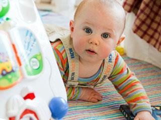大きな玩具に近づく赤ちゃん