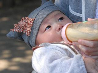 外で哺乳瓶でミルクを飲む赤ちゃん