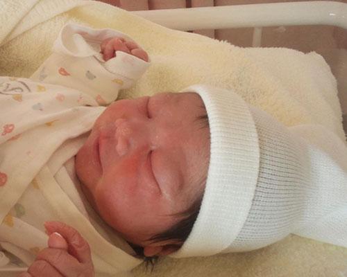 帽子を被らされた新生児