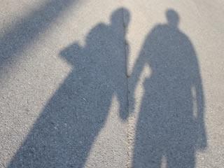 手を繋ぐカップルの影