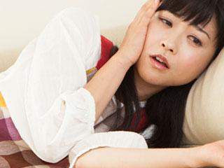 横になって顔を触る女性