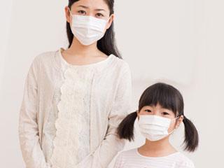 マスクをかけて並んで立つ親子