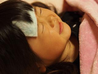 額にシートを張って寝込む子供