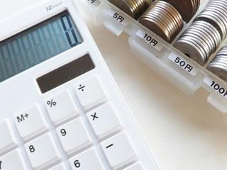 勘定計算される電卓と小銭
