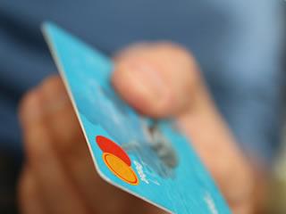 家族のクレジットカードでブランド品を買う妻