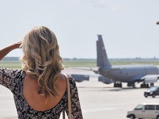 空港の滑走路を見つめる女性