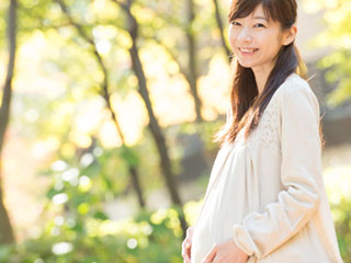 公園で散歩する妊婦