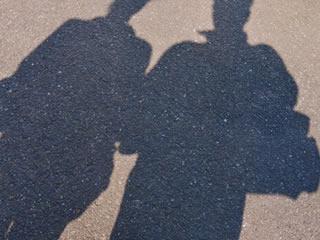 仲良く隣通しで歩く熟年夫婦の影
