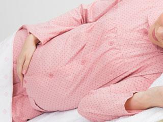 横になってお腹を押さえる妊婦