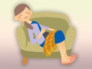 ひざ掛けをしてソファで休む女性