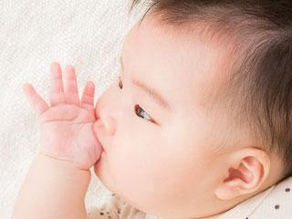 自分の親指を吸う赤ちゃん