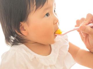 スプーンで離乳食を食べる乳児