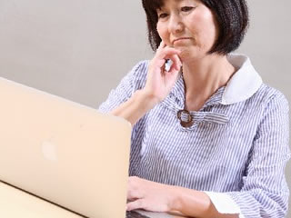 夫との不仲に悩む熟年離婚の方法を調べる女性
