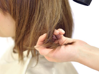 髪の毛にドライヤーを当てられる女性