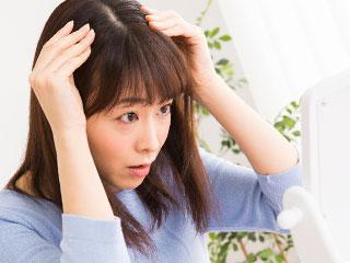 髪の分け目を見て心配する女性