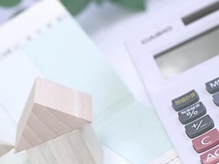 通帳と計算機で住宅ローンを計算中