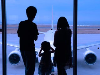 空港ロビーから飛行機を見る親子
