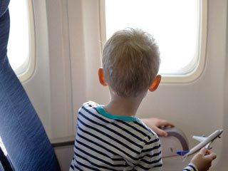 飛行機内から窓の外を見る子供