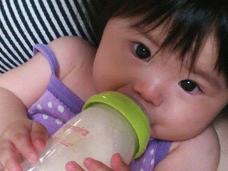 哺乳瓶を持ってミルクを飲む赤ちゃん