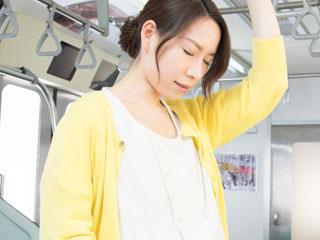 電車のつり革につかまりながら俯く妊婦