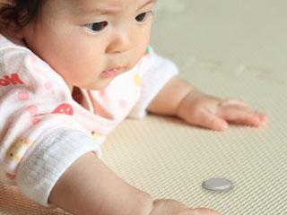 ボタン電池を見る赤ちゃん
