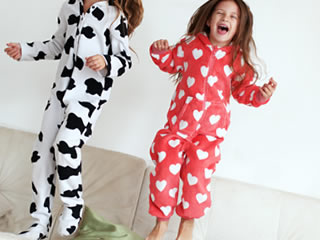 ソファーで元気に飛び回る可愛いパジャマの子供