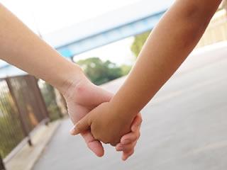 再婚相手の子供と手を繋ぎ仲良く歩く母親