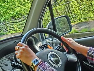 車のハンドルを操作する手