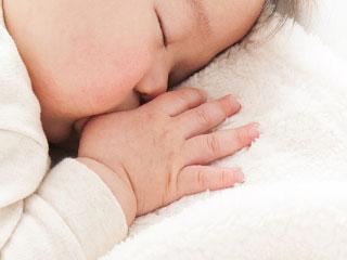 指を咥えながら居眠りする赤ちゃん