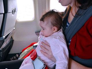 機内座席で赤ちゃんを抱っこする母親