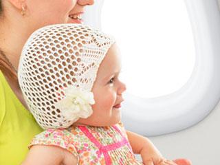 飛行機内座席に母親と座る赤ちゃん