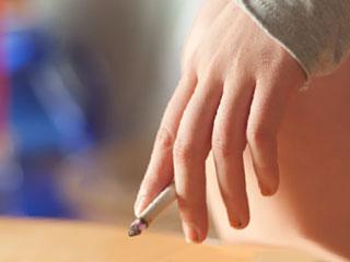 吸いかけのタバコを持つ手