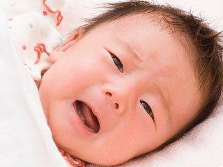 布団の中で目を開けている赤ちゃん