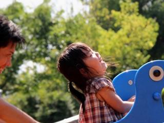 親と公園の乗り物で遊び喜ぶ子供