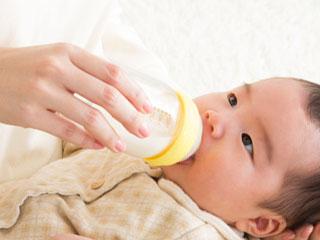 哺乳瓶を持って赤ちゃんに飲ませる母親