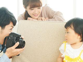赤ちゃんの写真を撮る血父親と見守る母親