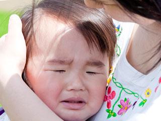 抱っこした赤ちゃんの顔を見る母親